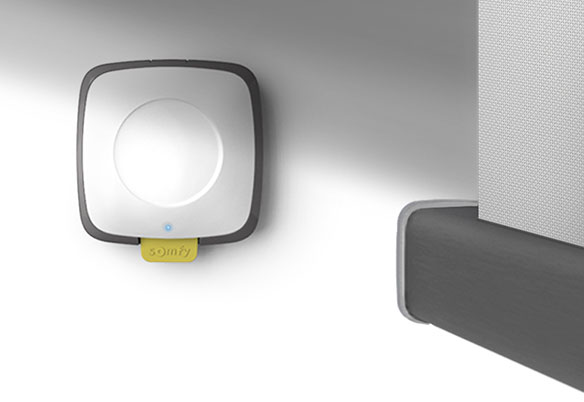 A Somfy light sensor positioned on an interior wall near a powered blind